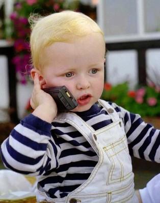 Barn der taler i mobiltelefon som en chef